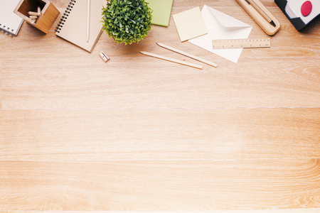 Topview of wooden desk with office tools and plant. Mock up Archivio Fotografico