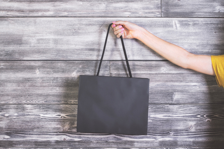 blank template: Female arm holding blank shopping bag on wooden background. Mock up