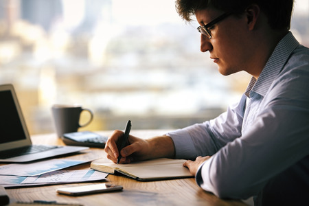 finacial: Sideview of businessman writing something down in copybook placed on wooden desktop with notebook, business reports, smartphone and other items