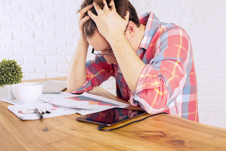 office chaos: Stressed caucasian male with head in hands over wooden desk with tablet, business charts and coffee mug on white brick wall background