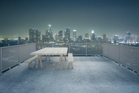 balcony view: Balcony design with table and benches, concrete floor and railing on illuminated night city background. 3D Rendering
