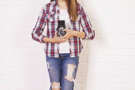 casually dressed: Casually dressed female holding retro camera on white brick background Stock Photo