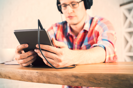 people watching: Blurry male with tablet in hands sitting at wooden desk and listening to music