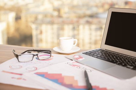 financial growth: Closeup of wooden desktop with blank laptop, business reports, glasses and coffee cup on blurry city background. Mock up