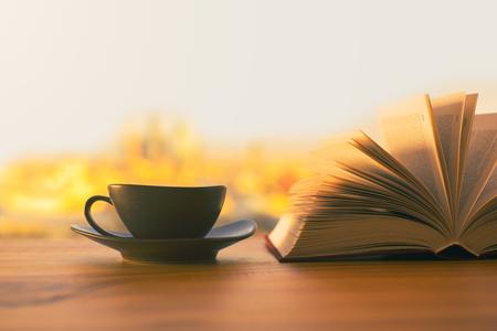 Tazza di caffè nero e libro aperto sul tavolo di legno con la città soleggiata sullo sfondo