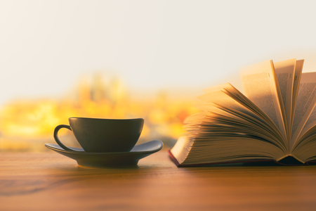 Black coffee cup and open book on wooden table with sunlit city in the background Stockfoto