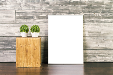 wooden surface: Blank picture frame and stand with two plants on wooden background. Mock up Stock Photo