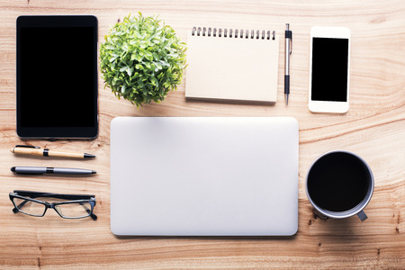 office supplies: Topview of wooden desk with neatly organized office tools and electronic gadgets. Mock up Stock Photo