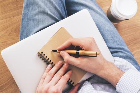 hombre escribiendo: Topview de la escritura hombre en el bloc de notas de edad coloca en la computadora portátil cerrada y café. fondo de madera