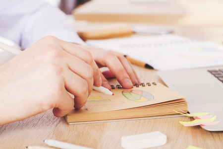 sideview: Sideview of male hand drawing business diagrams on wooden desktop Stock Photo