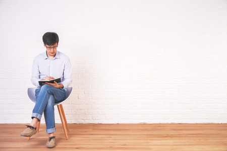 empty of people: Young caucasian male writing in notepad in interior with empty brick wall and wooden floor. Mock up