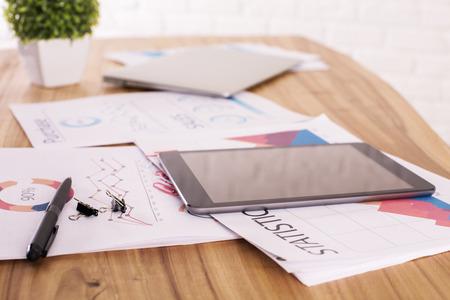 cuadro sinoptico: Primer de la mesa de madera con los informes de negocio, la pequeña planta verde y la tableta con pantalla en blanco Foto de archivo