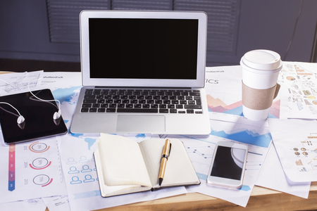 blank tablet: Office desktop with blank laptop, coffee, tablet and other items on business reports. Mock up