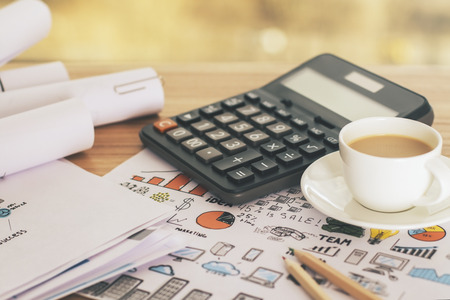 Wooden desktop with calculator and coffee cup on business concept sketch