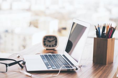 Seitenansicht der hölzernen Schreibtisch mit Laptop, Uhr, Bleistifthalter und andere Elemente Standard-Bild