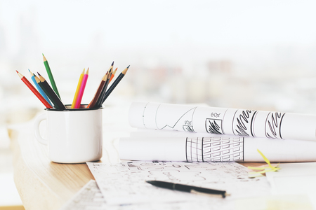 rolled paper: Iron mug with pencils on wooden desktop with sketches on rolled paper sheets