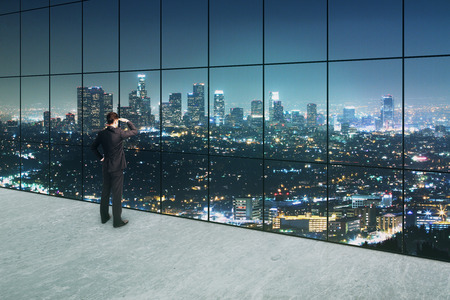 window view: Thoughtful businessman looking into the distance in interior with concrete floor and panoramic windows with illuminated night city view. 3D Rendering