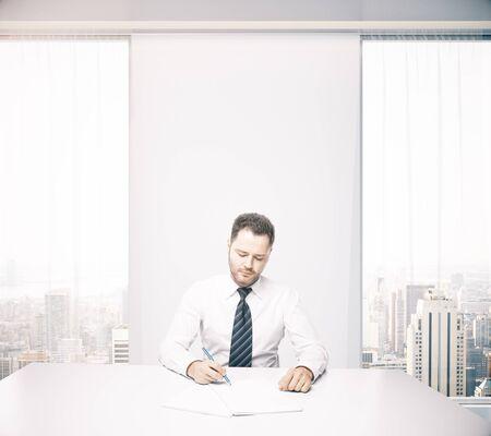 hombre escribiendo: Caucásico apuesto hombre de negocios sentado en el escritorio en la oficina con ventanas y vistas a la ciudad de Nueva York. Representación 3D