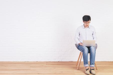 silla de madera: diseño de interiores de ladrillo con piso de madera y joven sentado en una silla con un ordenador portátil. Bosquejo