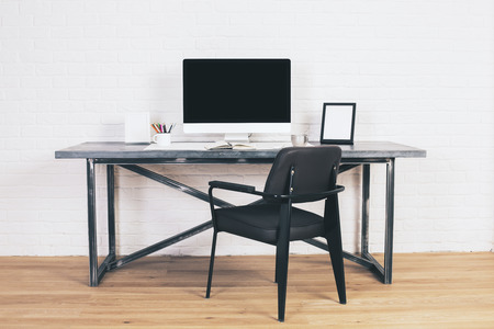 designer chair: Modern black chair at designer desk with blank computer screen and picture frames. Mock up