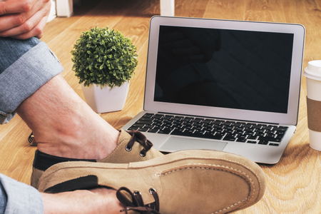 laptop home: Male feet on wooden floor next to blank notebook screen, coffee, plant and other items. Mock up Stock Photo