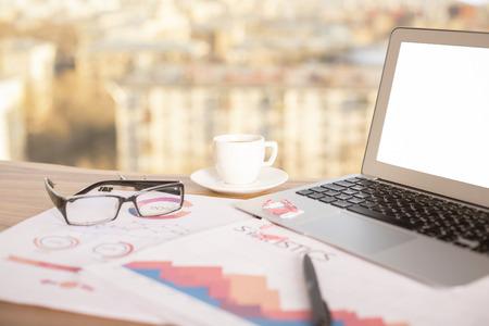 Gros plan du bureau en bois avec un ordinateur portable blanc blanc, des rapports d'affaires, des verres et tasse de café sur fond flou ville. Maquette