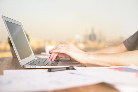 Lateral de las manos femeninas que pulsan en la computadora portátil con pantalla en blanco, colocado en el escritorio de madera con hojas de papel borrosas. ciudad iluminada por el sol en el fondo. Bosquejo