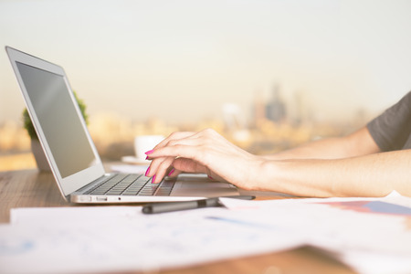 Sideview of female hands typing on laptop with blank screen, placed on wooden desktop with blurry paper sheets. Sunlit city in the background. Mock up