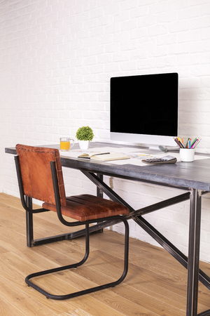 designer chair: Sideview of desk with blank computer screen and brown chair next to it on wooden floor and brick background