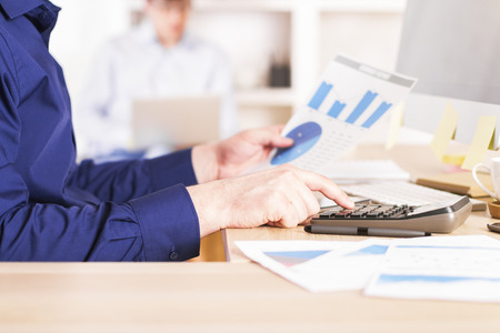sideview: Sideview of businessman using calculator on business diagrams