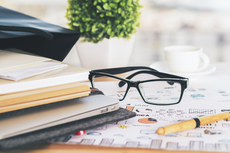 designer bag: Closeup of desk with notepads, glasses and plant on business concept sketch