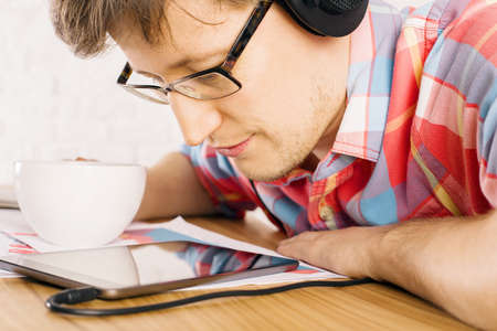 closely: Caucasian male with glasses and blank coffee cup in hand looking at tablet screen very closely