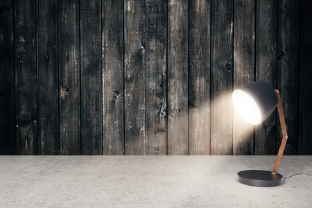 turned: Concrete surface and aged wooden wall with small, turned on table lamp. Mock up, 3D Renderin