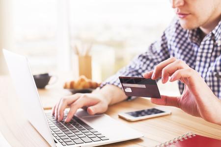 Online winkelen en betalingsconcept met mannetje bij bureau het typen op computertoetsenbord en het houden van een creditcard Stockfoto