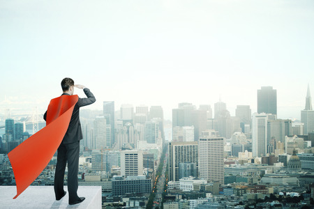 invincible: Businessman with red superhero cape standing on pedestal and looking into the distance on cityscape background