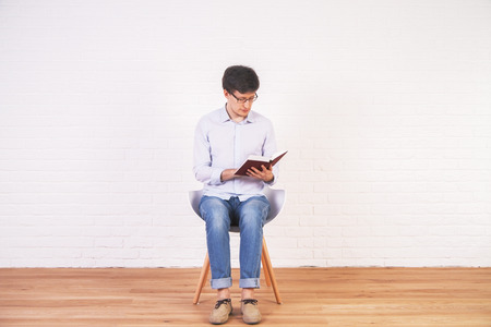 stool test: Young caucasian male reading a book in interior with brick wall and wooden floor