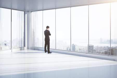executive: Thoughtful businessman standing in empty room with panoramic windows and New York city view. 3D Rendering