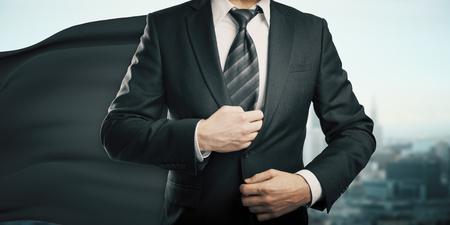 invincible: Businessman with black superhero cape on city background