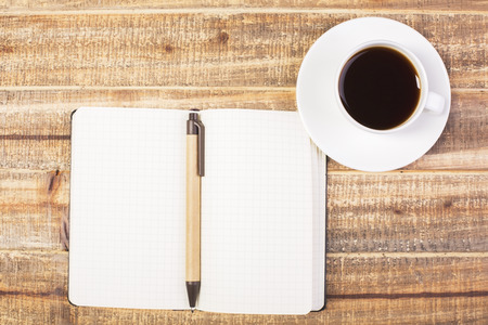 up view: Topview of blank notepad with pen and coffee cup on antique wooden desktop