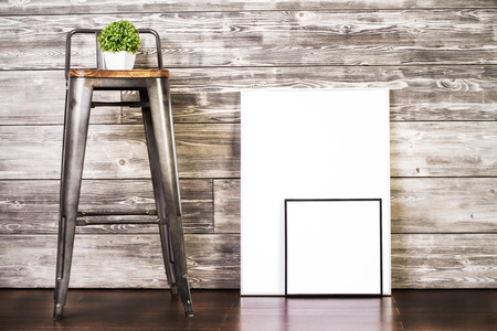 Blank Bilderrahmen und Hocker mit Pflanze auf Holzuntergrund. Attrappe, Lehrmodell, Simulation