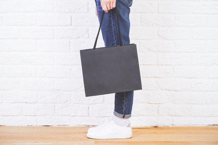 sideview: Sideview of female legs with blank shopping bag on white brick wall. Mock up Stock Photo