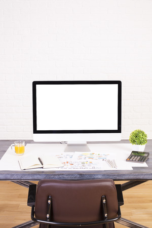designer chair: Designer tabletop with blank computer monitor and other office tools with a brown chair back showing. Wooden floor and white brick background. Mock up Stock Photo