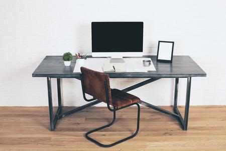 Vista frontale della scrivania di design con monitor vuoto, cornici e altri oggetti con sedia marrone accanto ad essa. pavimento in legno e sfondo bianco muro di mattoni. Modello