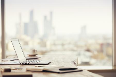 oficina: Lateral de escritorio de oficina con ordenador portátil en blanco y varias herramientas de oficina a fondo borroso de la ciudad de Moscú