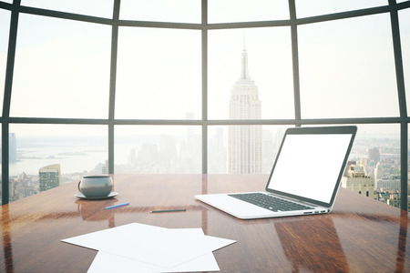 workspace: Closeup of shiny wooden desktop with blank white laptop, coffee cup and paper sheets with window and New York city view in the background. Mock up, 3D Rendering