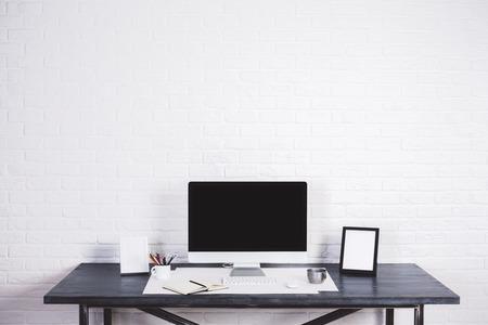 Designer desktop met een leeg computerscherm, fotolijstjes en andere items op witte bakstenen achtergrond. Mock up