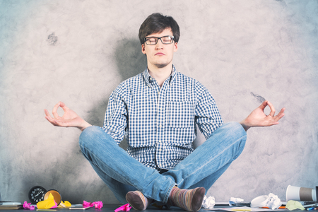 man meditating: Handsome caucasian man meditating on messy desktop with concrete wall in the background
