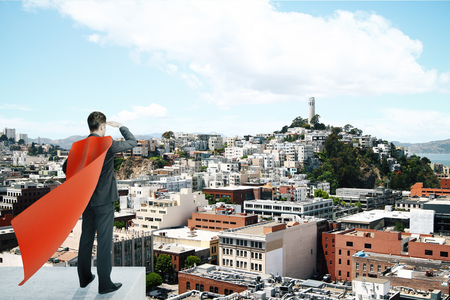 distance: Businessman with red superhero cape standing on pedestal and looking into the distance on bright cityscape background