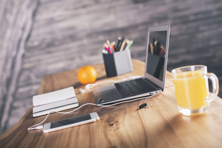 Side view of designer desk with laptop, smartphone, office tools and orange Stockfoto