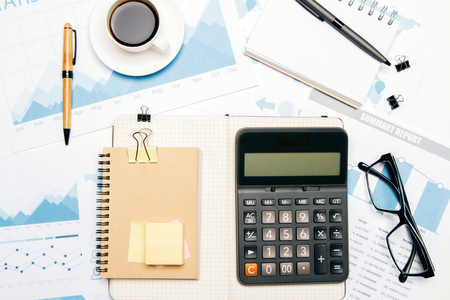 Topview of office desktop with business report, calculator and other tools